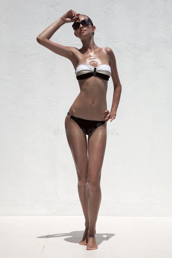 Красивая tan женская модель представляя в бикини и солнечных очках стоковые изображения