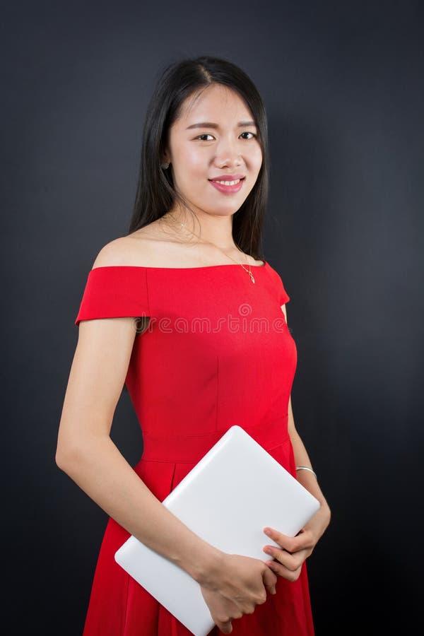 Красивейшая азиатская женщина держа компьтер-книжку стоковое изображение