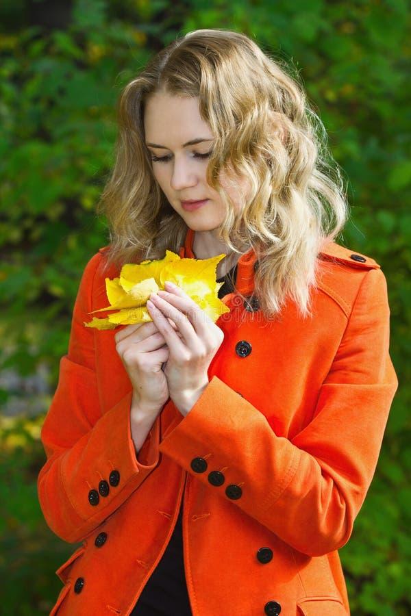 Красивейшая белокурая девушка с пуком листьев стоковая фотография
