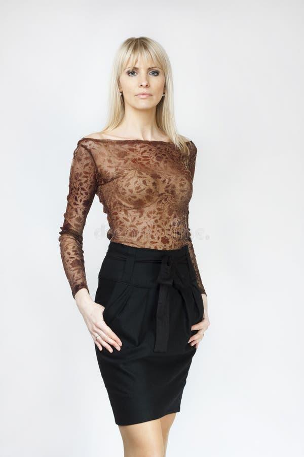 Красивейшая белокурая женщина в черной миниой юбке стоковая фотография rf