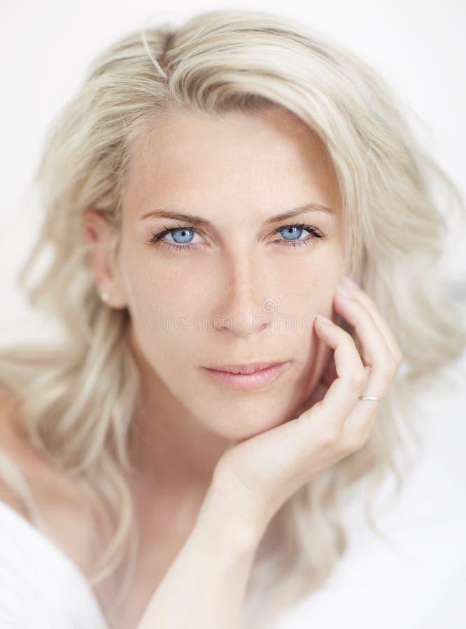 Красивейшая белокурая женщина, голубой глаз, белое bacground, стоковое фото