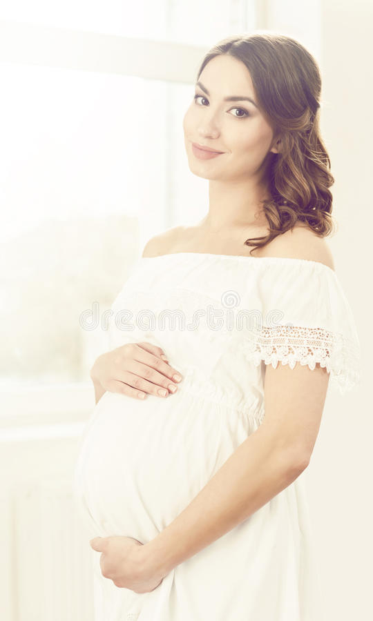 Красивейшая беременная женщина в белом платье Материнство, беременность, стоковые фотографии rf