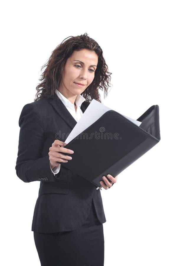 Красивейшая возмужалая коммерсантка читая рапорт стоковое изображение rf