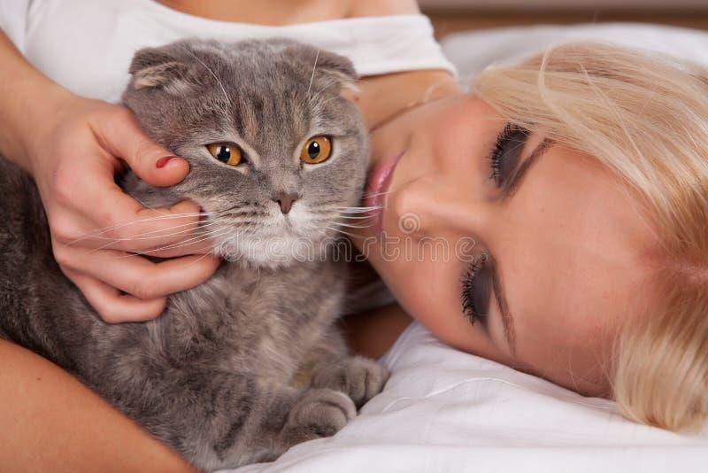 красивейшая девушка большого кота кровати идет к стоковые фотографии rf