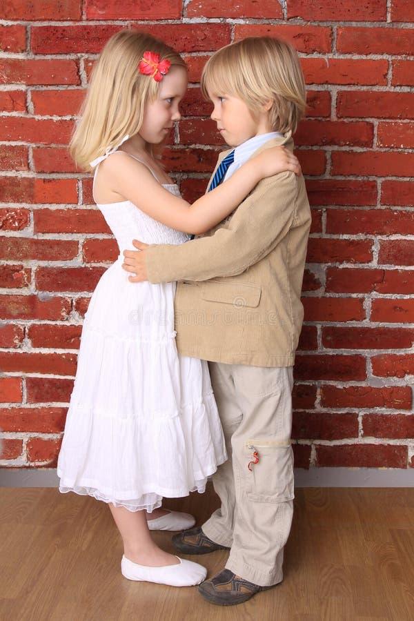 красивейшая девушка мальчика обнимая немного стоковая фотография