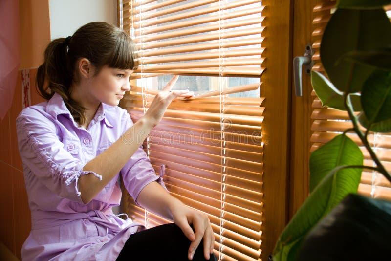 красивейшая девушка смотрит вне окно стоковое изображение rf