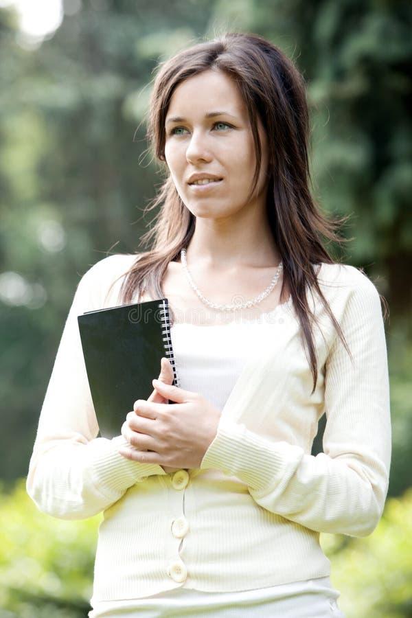 Красивейшая девушка студента держа тетрадь стоковое фото rf