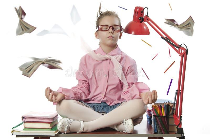 Schoolirl meditating на столе стоковое изображение rf