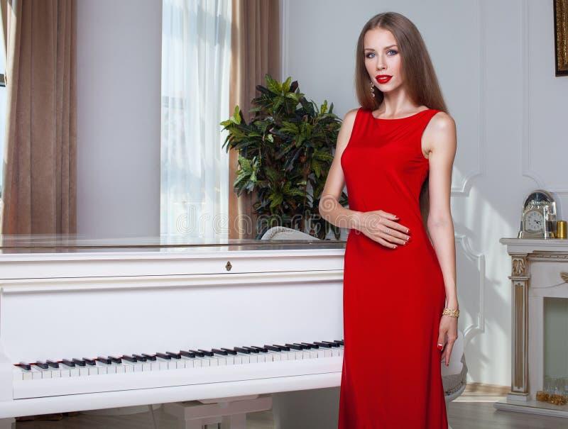 Красивейшая женщина брюнет в красном платье красивейшие детеныши женщины студии съемки танцы пар волосы длиной губы красные стоковая фотография