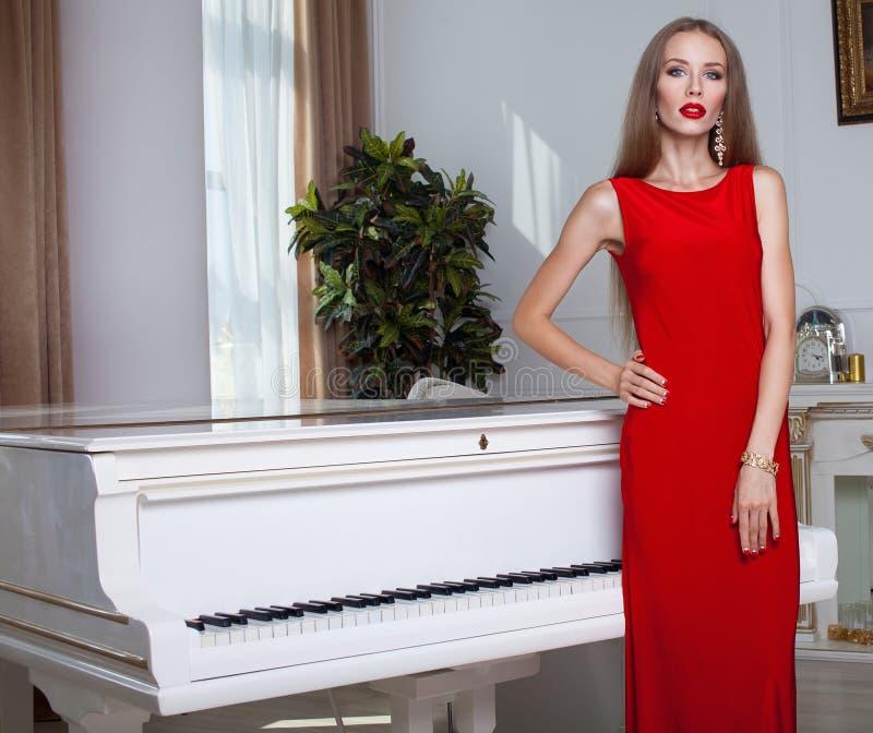 Красивейшая женщина брюнет в красном платье красивейшие детеныши женщины студии съемки танцы пар волосы длиной губы красные стоковая фотография rf