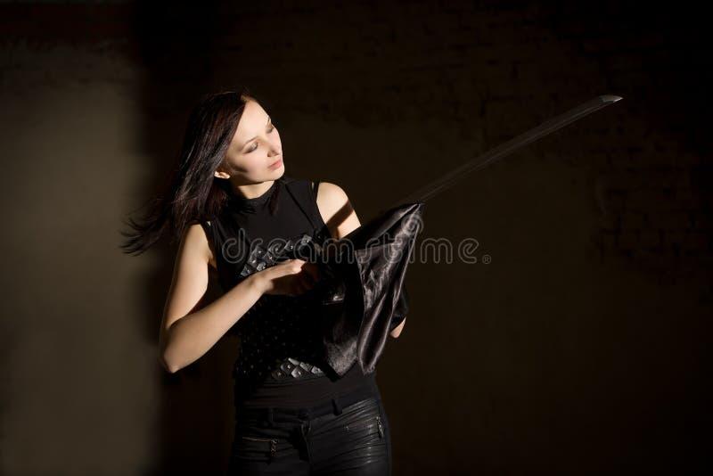 Красивейшая женщина в кожаном saber удерживания одежды стоковое фото rf