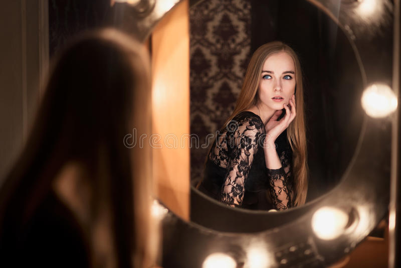 Красивейшая женщина модели способа представляя около зеркала стоковая фотография rf
