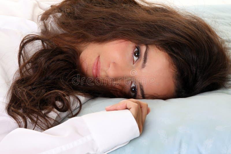 красивейшая женщина релаксации кровати стоковое изображение