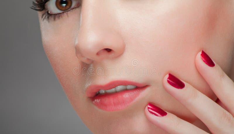 Красивейшая женщина с красным ногтем стоковое изображение