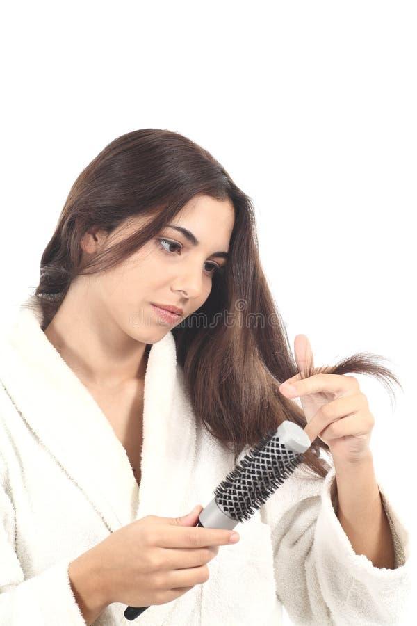 Красивейшая женщина с щеткой для волос наблюдая ее волос стоковое фото rf