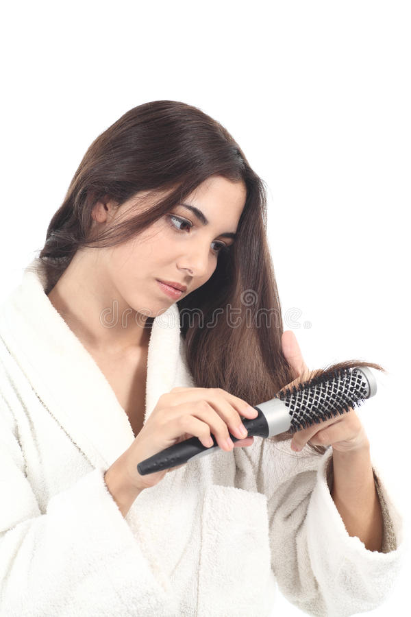 Красивейшая женщина с щеткой для волос наблюдая и расчесывая ее волос стоковое фото