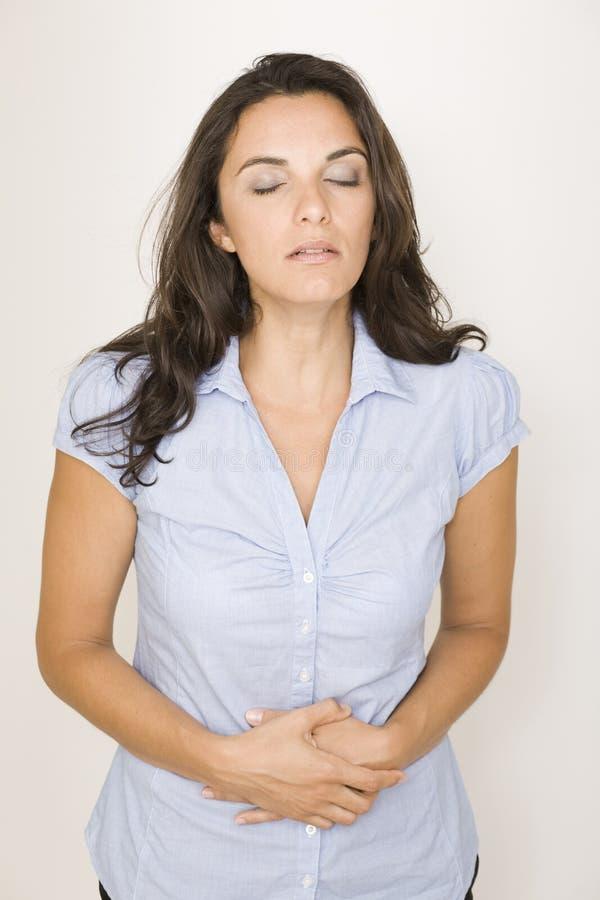 Красивейшая женщина терпя от stomachache стоковые фото