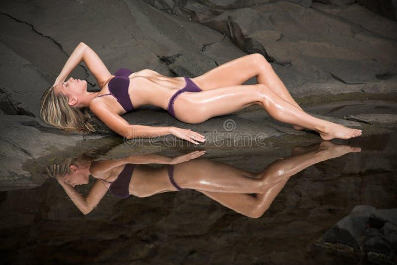 Красивейшая и сексуальная женщина лежит на утесах рядом с wat стоковые изображения
