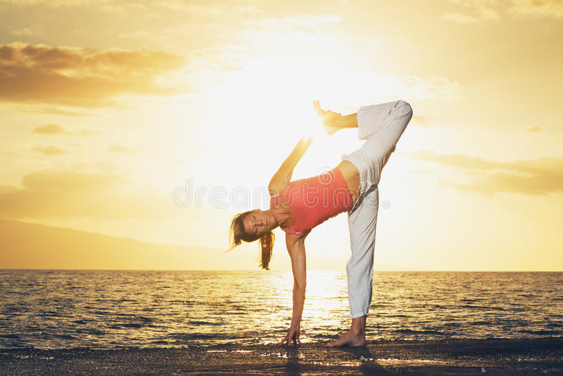 красивейшая йога женщины захода солнца стоковое изображение