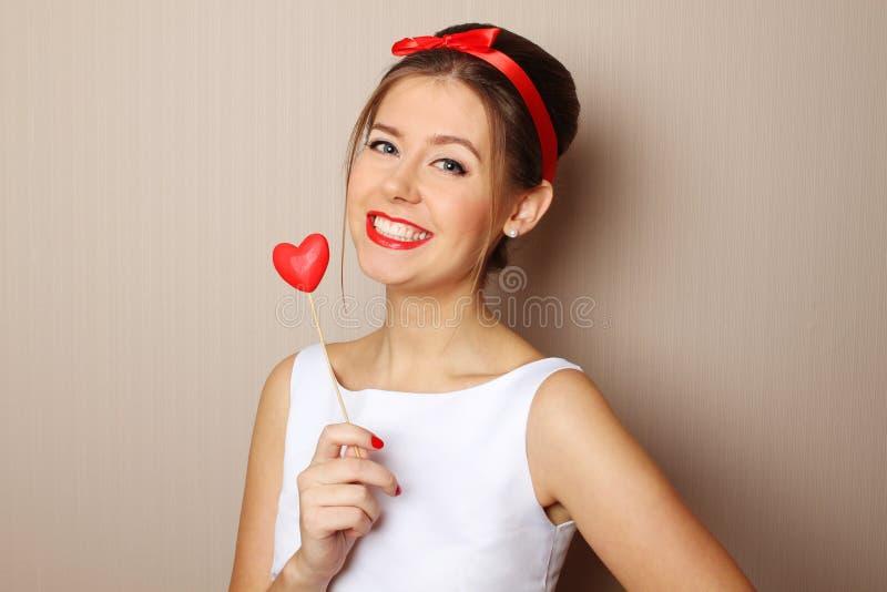 Красивейшая молодая женщина держа красное сердце стоковые изображения rf