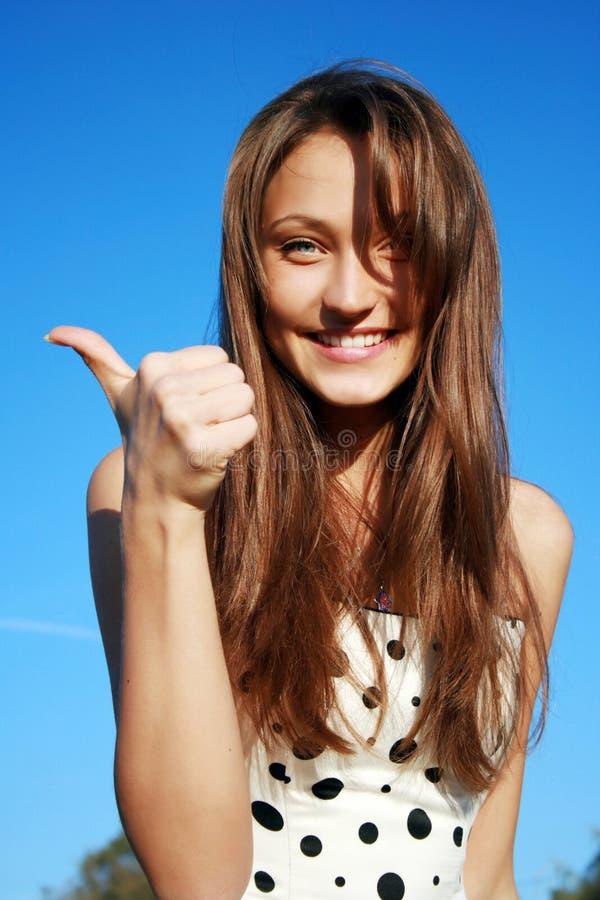 Красивейшая молодая женщина показывая большие пальцы руки поднимает si стоковые изображения rf