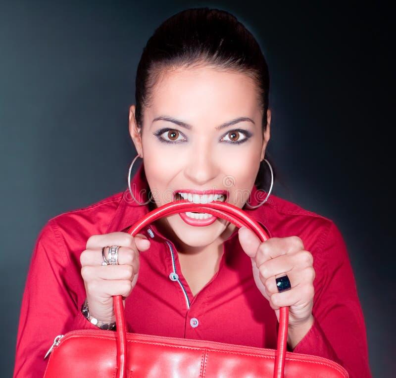 Красивейшая молодая женщина с красным мешком в зубах стоковое изображение