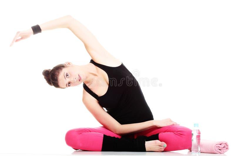 Красивейшая молодая женщина брюнет протягивая изолированные рукоятки мышц стоковые изображения rf