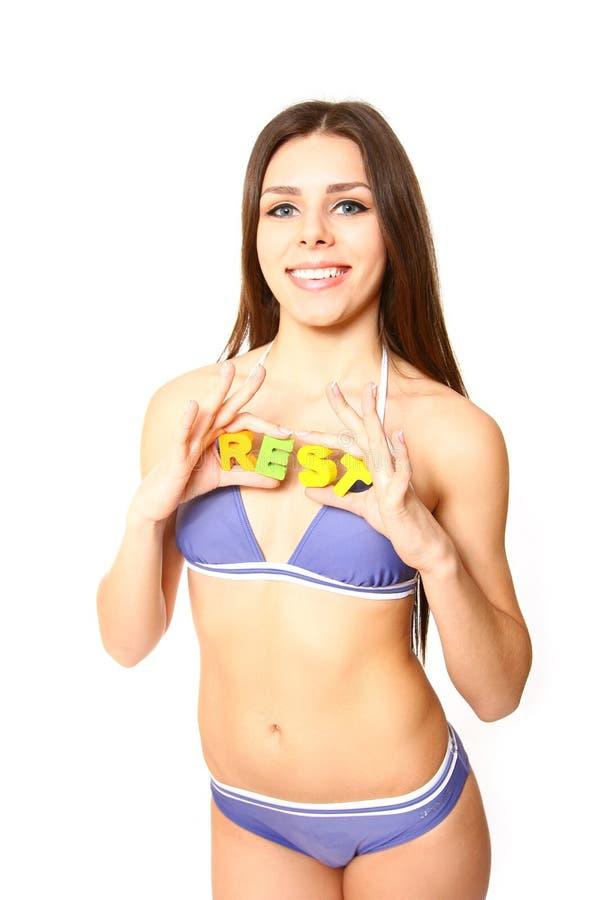 Красивейшая молодая женщина держа слово - отдохните на белой предпосылке стоковые фото