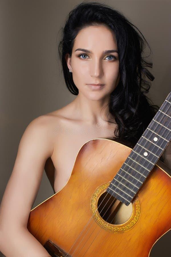 Красивейшая молодая женщина с гитарой стоковые изображения rf