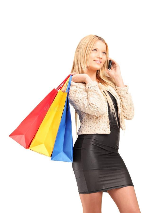 Красивейшая молодая женщина с хозяйственными сумками говоря на телефоне стоковое фото