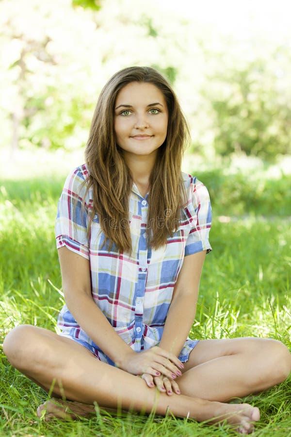 Красивейшая предназначенная для подростков девушка в парке на зеленой траве. стоковые фото