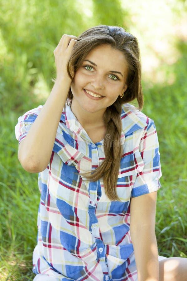 Красивейшая предназначенная для подростков девушка в парке на зеленой траве. стоковое фото