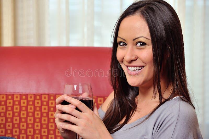 Красивейшая biracial женщина с стеклом красного вина стоковая фотография