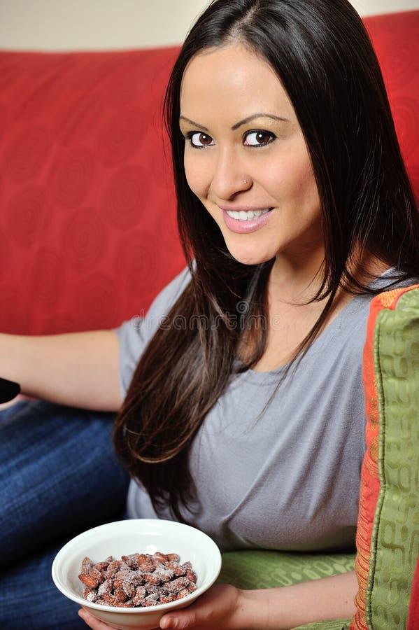 Красивейшая biracial женщина с шаром полным миндалин стоковая фотография rf