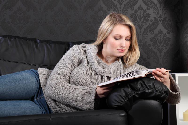 красивейшие белокурые детеныши женщины чтения дома книги стоковые изображения rf