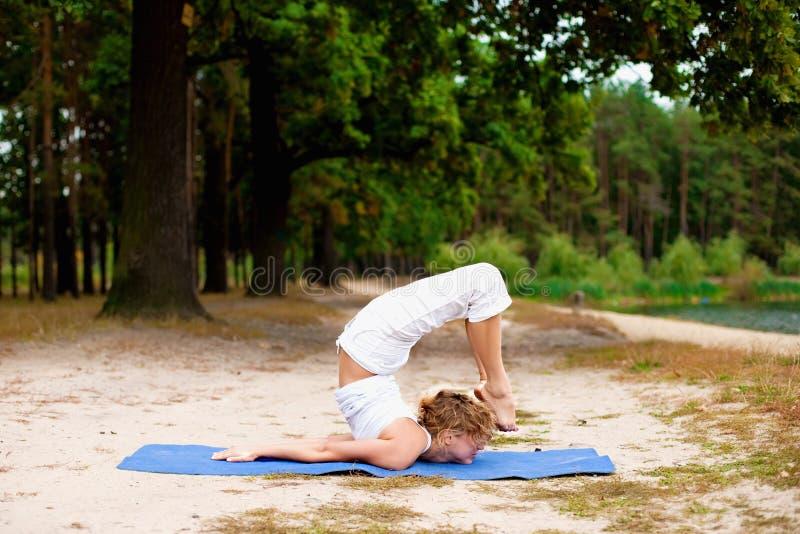 красивейшие делая детеныши йоги женщины тренировки outdoors стоковые фотографии rf
