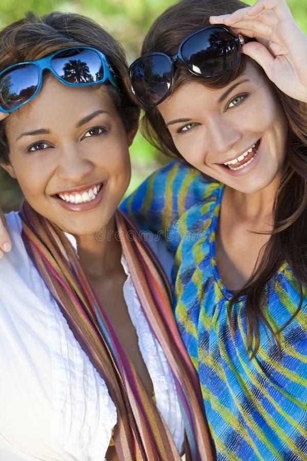 красивейшие друзья смеясь над 2 женщинами молодыми стоковое фото rf