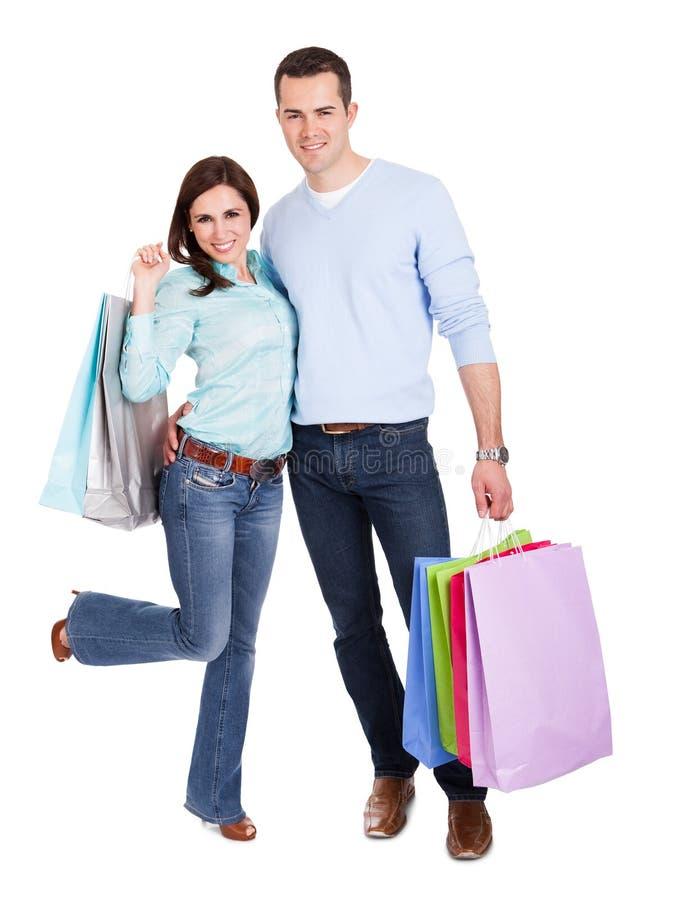 Красивейшие молодые пары с хозяйственными сумками стоковая фотография