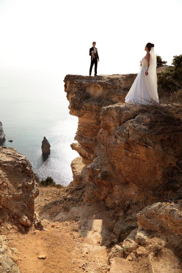 красивейшие пары шикарная невеста в платье свадьбы представляя с элегантным groom на цене моря стоковые фотографии rf