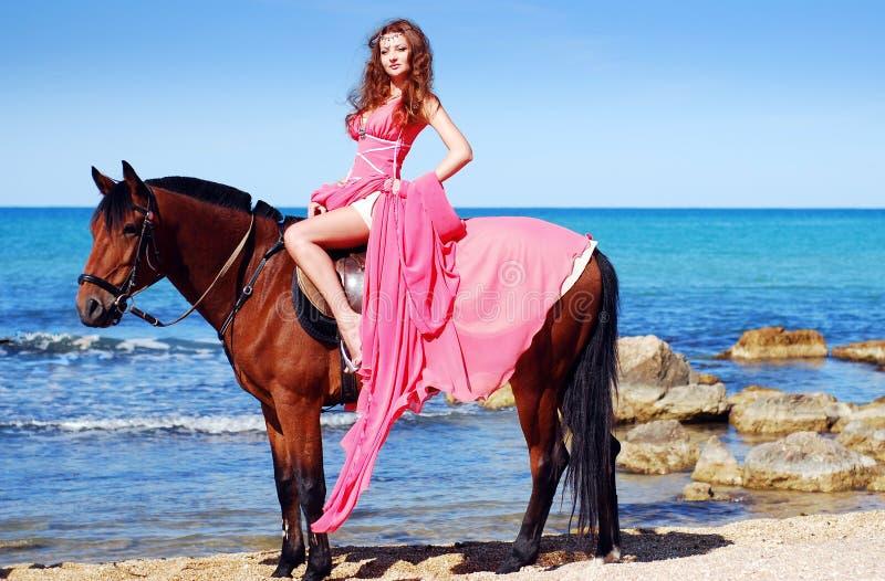 красивейший красный цвет лошади девушки платья сидит стоковое фото rf