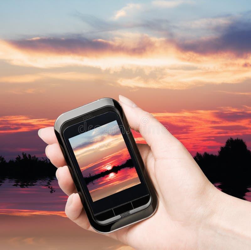 красивейший мобильный телефон извлекает заход солнца стоковое фото