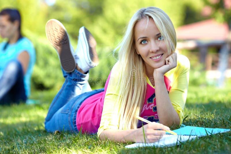 Красивейший студент лежит на зеленой лужайке и учит стоковая фотография