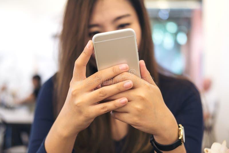 Красивое азиатское удерживание бизнес-леди, использующ и смотрящ умный телефон в современном кафе стоковые фото