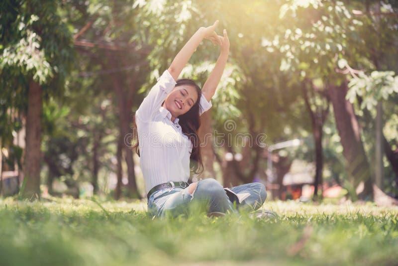 Красивое азиатское усаживание молодой женщины и ослаблять на поле внутри стоковая фотография