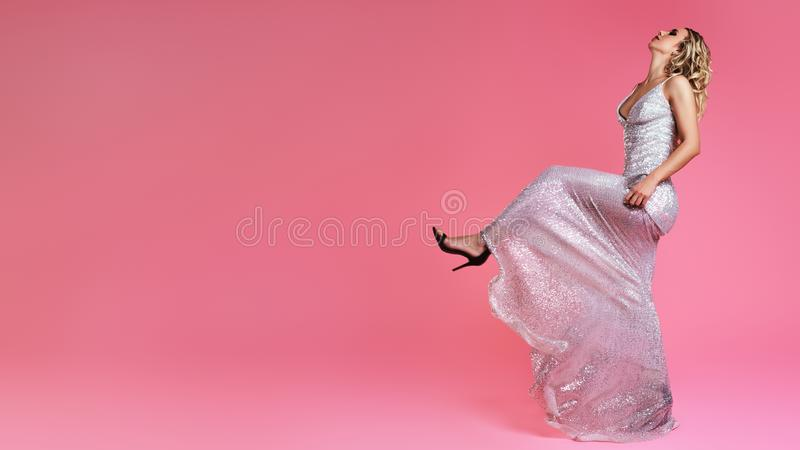 Красивое белокурое в платье моды Сексуальная женщина маршируя на предпосылку подиума моды розовую Роскошные одежды блеска, ботинк стоковая фотография