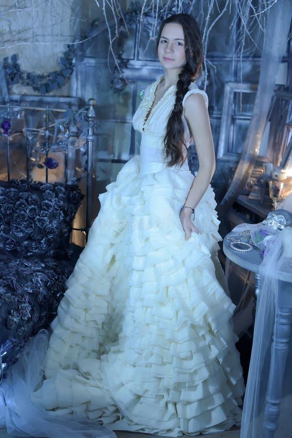 Красивое брюнет в белом платье в винтажном интерьере стоковые фотографии rf