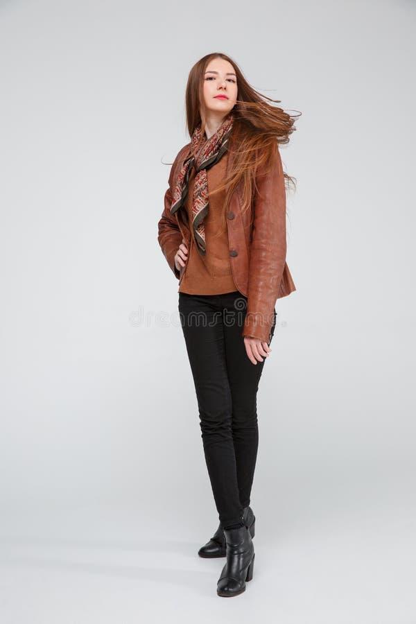 Красивое брюнет в коричневой кожаной куртке представляя положив ногу на ногу против серой предпосылки стоковое изображение