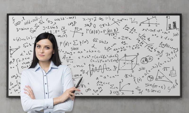Красивое брюнет обдумывает о решении осложненной аналитической проблемы Формулы математики написаны вниз на whit стоковые фотографии rf