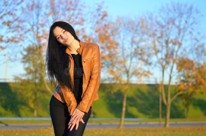 Красивое брюнет представляя на красочном парке осени стоковое фото