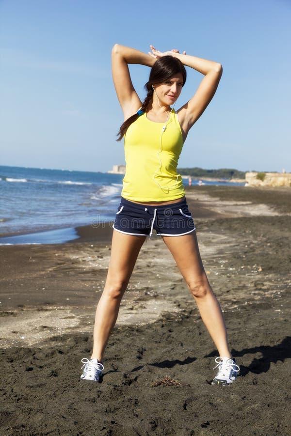 Красивое брюнет протягивая на пляже после jogging стоковая фотография rf